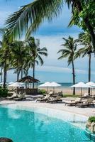 sedie piscine o lettini e ombrelloni intorno alla piscina con sfondo mare - vacanze e concetto di vacanza vacation foto