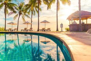 bellissimi ombrelloni e sedie di lusso intorno a una piscina all'aperto in hotel e resort con palme da cocco sul cielo al tramonto o all'alba - concetto di vacanza e vacanza foto