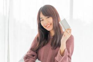 donna asiatica che tiene la pillola anticoncezionale foto