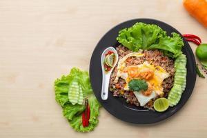 riso fritto con gamberi in piatto nero sul tavolo foto