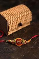 sfondo raksha bandhan con un elegante rakhi, chicchi di riso, kumkum e confezione regalo. un tradizionale cinturino da polso indiano che è un simbolo di amore tra fratelli e sorelle. foto