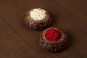 kumkum e contenitore del chicco di riso. le polveri di colore naturale vengono utilizzate durante il culto di Dio e in occasioni di buon auspicio. foto