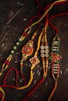sfondo raksha bandhan con un elegante rakhi e riso sparso. un tradizionale cinturino da polso indiano che è un simbolo di amore tra fratelli e sorelle. foto