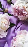 fiori di peonia su uno sfondo di seta viola foto