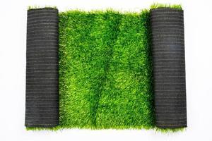 Rotolo di erba verde artificiale isolato su sfondo bianco, prato, copertura per campi sportivi foto