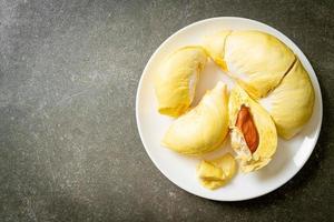 durian stagionato e fresco, buccia di durian su piatto bianco foto