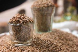semi di cumino in vetro al mercato locale, spezie indiane foto