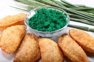 gujia con colore verde holi su sfondo bianco insieme a foglie di cipolla verde foto