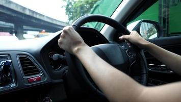 immagini ravvicinate delle mani della donna che guidano l'auto con fiducia. foto
