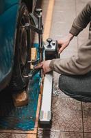 primo piano di un pneumatico bloccato da un livellatore che passa l'allineamento automatico delle ruote in garage, garage e strumenti per il meccanico. foto
