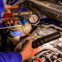 meccanico professionista che lavora in un servizio di auto, diagnostica computerizzata dello spazio del cofano nell'auto. foto
