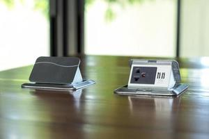 primo piano coppia di prese elettriche pop-up installate sulla superficie del tavolo di legno in ufficio foto