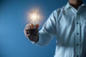 mano uomo d'affari che tiene lampadina, innovazione e concetto di ispirazione foto