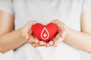 le mani della donna che tengono il cuore rosso con il segno del donatore di sangue. concetto di assistenza sanitaria, medicina e donazione di sangue foto