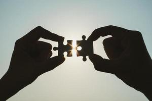 siluetta della mano dell'uomo e della donna del primo piano che collega un pezzo di puzzle sopra l'effetto di luce solare. simbolo di associazione e concetto di connessione. strategia d'affari. foto