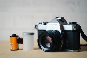 vecchia fotocamera a pellicola reflex e un rotolo di pellicola su sfondo di legno. foto