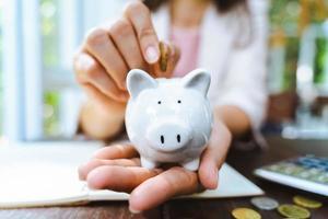 primo piano della mano della donna di affari che mette moneta dei soldi nel salvadanaio per risparmiare soldi. risparmio di denaro e concetto finanziario foto