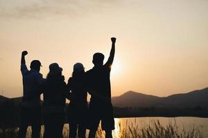 gruppo di persone con le braccia alzate che guardano l'alba sullo sfondo della montagna. felicità, successo, amicizia e concetti di comunità. foto