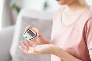 donna asiatica che controlla il livello di zucchero nel sangue tramite glucometro digitale, assistenza sanitaria e medica, diabete, concetto di glicemia foto
