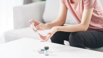 donna asiatica che usa la lancetta sul dito per controllare il livello di zucchero nel sangue mediante glucometro, assistenza sanitaria e medica, diabete, concetto di glicemia foto