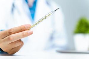 il medico tiene in mano un termometro a mercurio medico in ospedale. strumento ospedaliero, attrezzatura. concetto di assistenza sanitaria e medica. foto