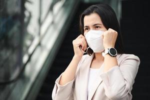 donna asiatica che indossa la maschera n95 per proteggere l'inquinamento pm2.5 e virus. covid-19 concetto di coronavirus e inquinamento atmosferico pm2.5. foto