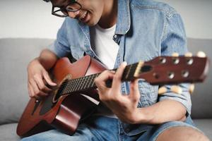 goditi un bell'uomo asiatico che si esercita o suona la chitarra sul divano del soggiorno foto