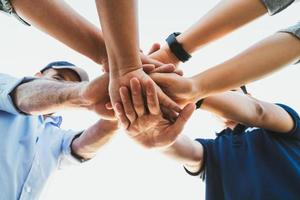 persone che uniscono le mani. amici con una pila di mani che mostrano unità e lavoro di squadra. concetto di squadra di amicizia felicità tempo libero partenariato. foto