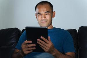 uomo seduto sul divano, utilizzando il computer tablet per lavoro o rilassarsi a casa. lavorare da casa concetto. foto
