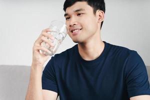 bell'uomo asiatico che beve un bicchiere d'acqua sul divano del soggiorno foto