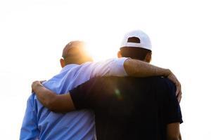 primo piano di amici maschi e femmine che si abbracciano guardando l'alba. felicità, successo, amicizia e concetti di comunità. foto