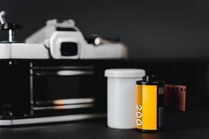 vecchia fotocamera a pellicola reflex e un rotolo di pellicola su sfondo nero, concetto di fotografia. foto