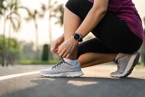 primo piano del corridore della giovane donna che lega i suoi lacci delle scarpe. concetto sano e fitness. foto