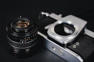 vecchia fotocamera a pellicola reflex e un obiettivo su sfondo nero, concetto di fotografia. foto