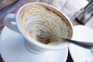 tazza bianca con avanzi di caffè sul tavolo foto