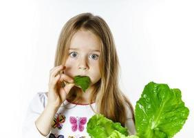 bambina carina in posa con foglie di insalata fresca foto