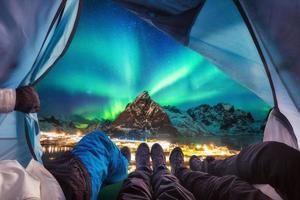 il gruppo di scalatori è all'interno del campeggio con l'aurora boreale sopra la montagna foto