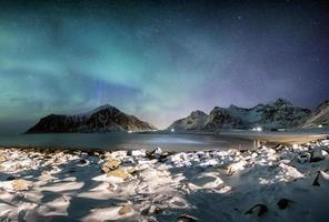 panorama dell'aurora boreale con stelle sulla catena montuosa con coste innevate foto