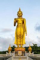 Una statua dorata del Buddha con il cielo sulla cima della montagna al parco pubblico del comune di Hat Yai, provincia di Songkhla, Thailandia foto