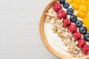 ciotola di yogurt fatta in casa con lampone, mirtillo, mango e muesli - stile alimentare sano foto