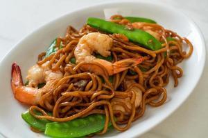 noodles yakisoba saltati in padella con piselli e gamberi - stile asiatico food foto