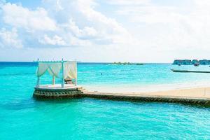 arco bianco con resort tropicale delle Maldive e sfondo del mare foto