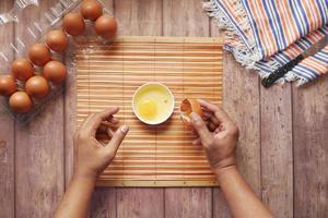 uomo che rompe l'uovo e lo versa in un piccolo contenitore sul tavolo foto