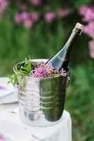 una bottiglia di champagne nuziale in un secchiello del ghiaccio su un tavolo foto