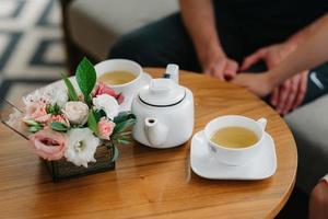 tè che beve tè nero con tazze di porcellana e teiera foto