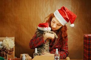 donna in cappello di babbo natale con gatto in cappello di natale. foto