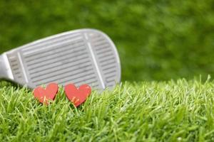 due cuori rossi di un giocatore di golf con fondo in ferro su erba verde on foto
