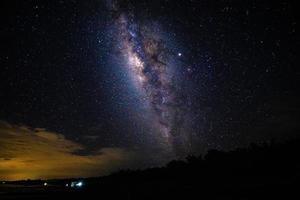 paesaggio notturno con la via lattea e luce da casa in montagna in thailandia foto