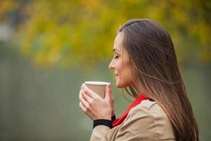 donna castana con una tazza di caffè nel parco autunnale. foto