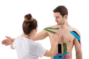 Fisioterapista femminile che mette il nastro kinesio sulla spalla del paziente foto